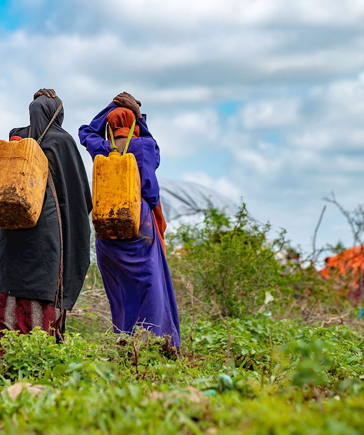 Women carrying bottles of water
