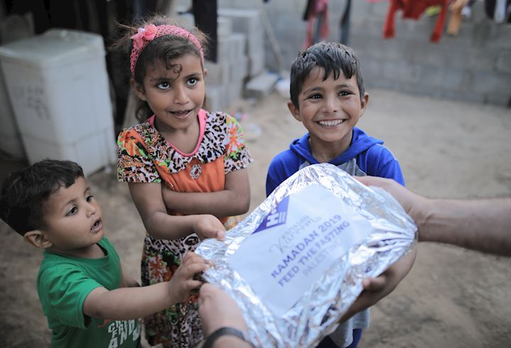 Young children receiving food over Ramadan