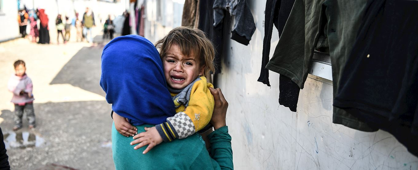 Syrian mother with crying child in her arms