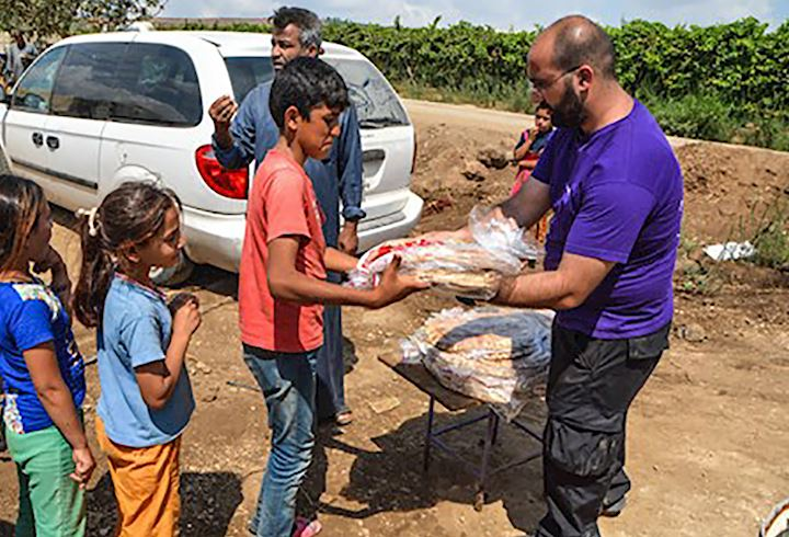 human appeal helper handing out food to children