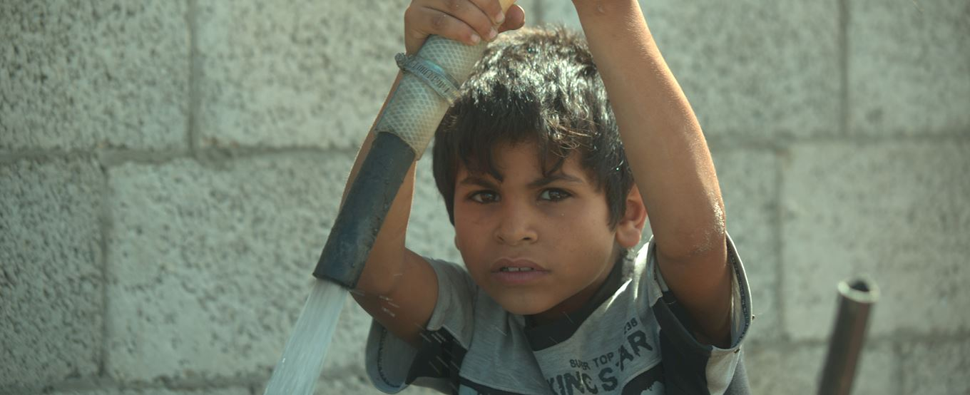 Young Gaza boy pouring water