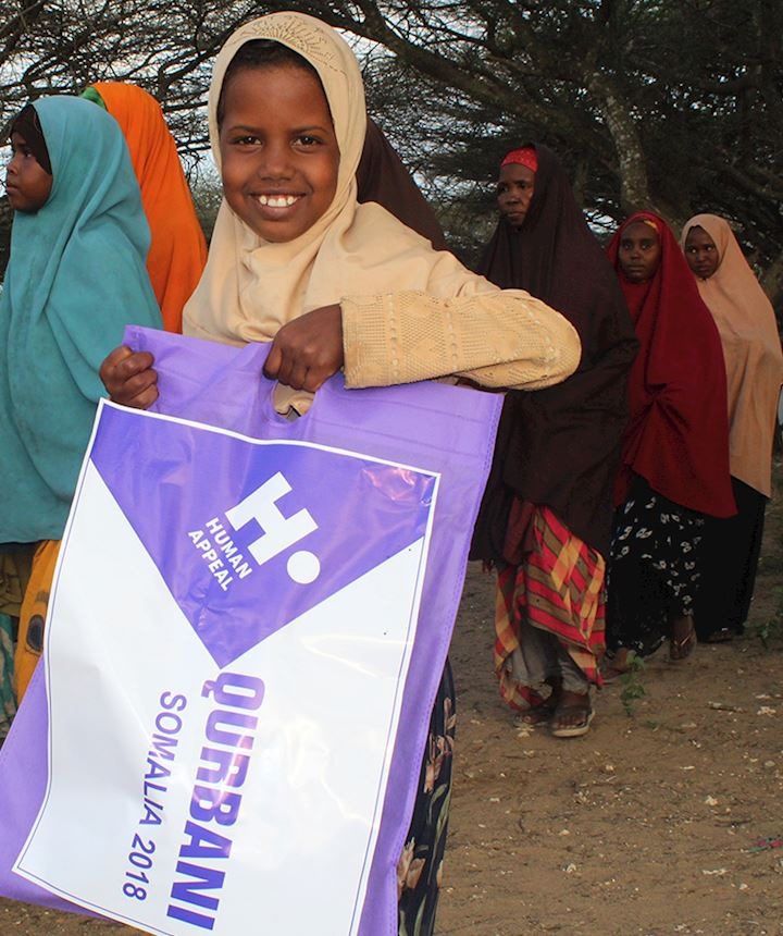 young somalia girl holding a human appeal bag and smiling