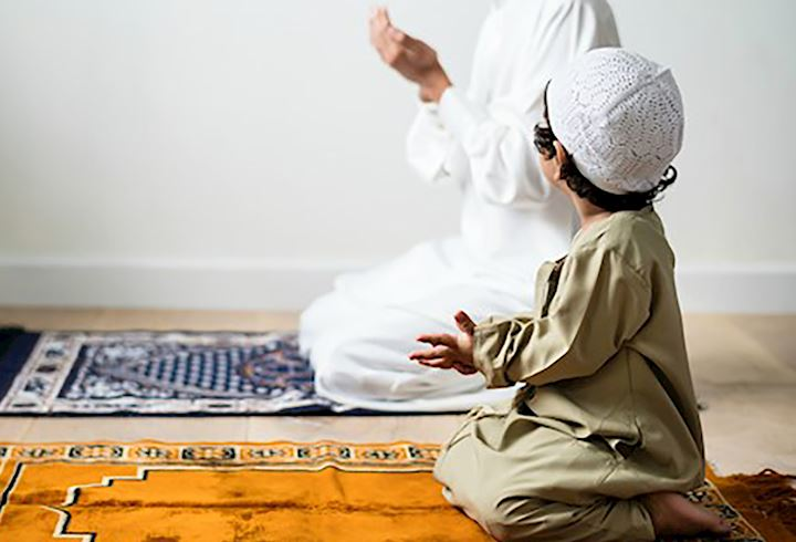small boy watching an adult pray