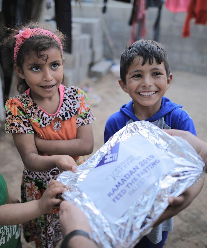 Young children receiving food over Ramadan