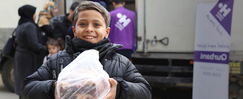 Young Palestinian boy holding fresh Qurbani meat