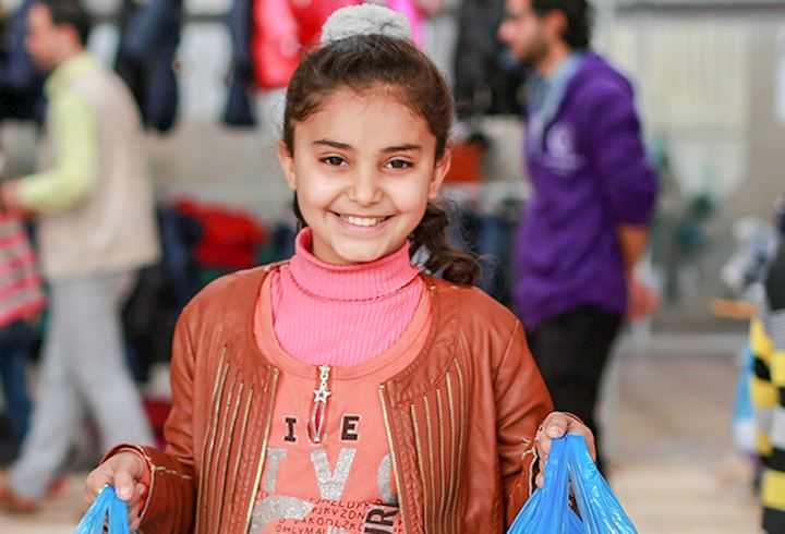 young girl holding to large human appeal clothes bags