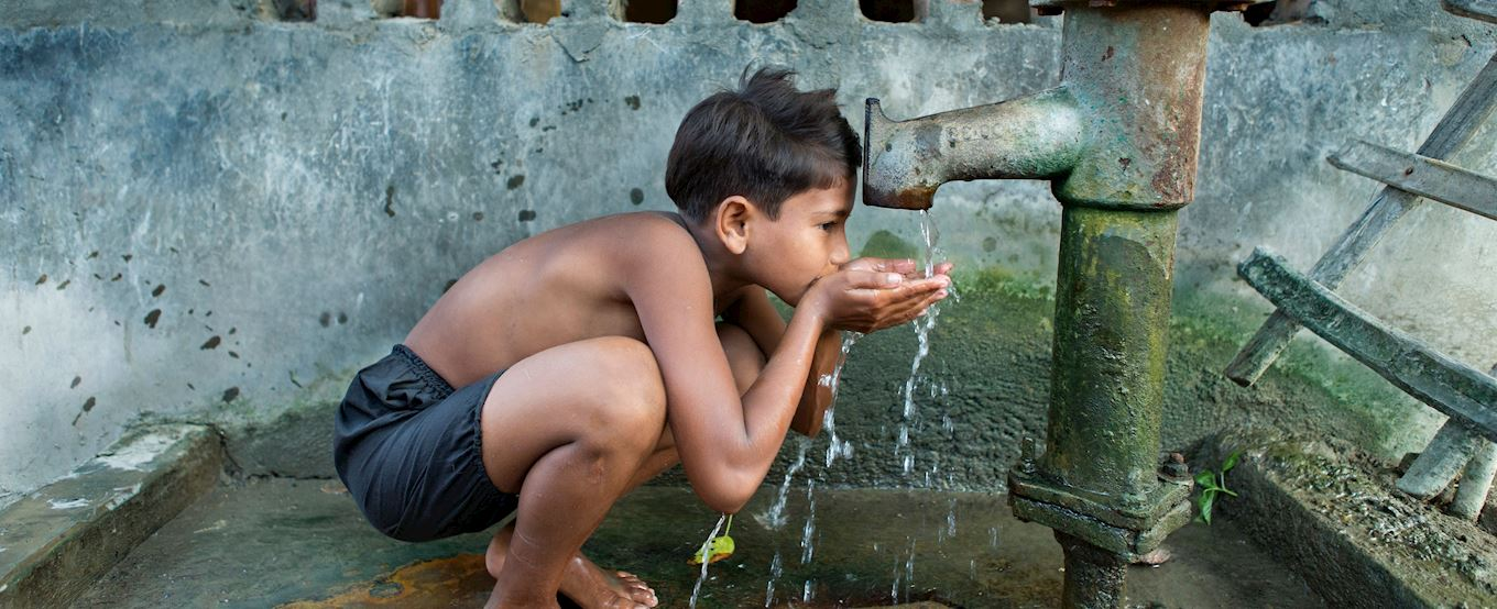Bangladeshi boy drinking water from a well