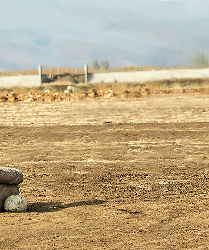 small child alone in a field on a chair - Syria