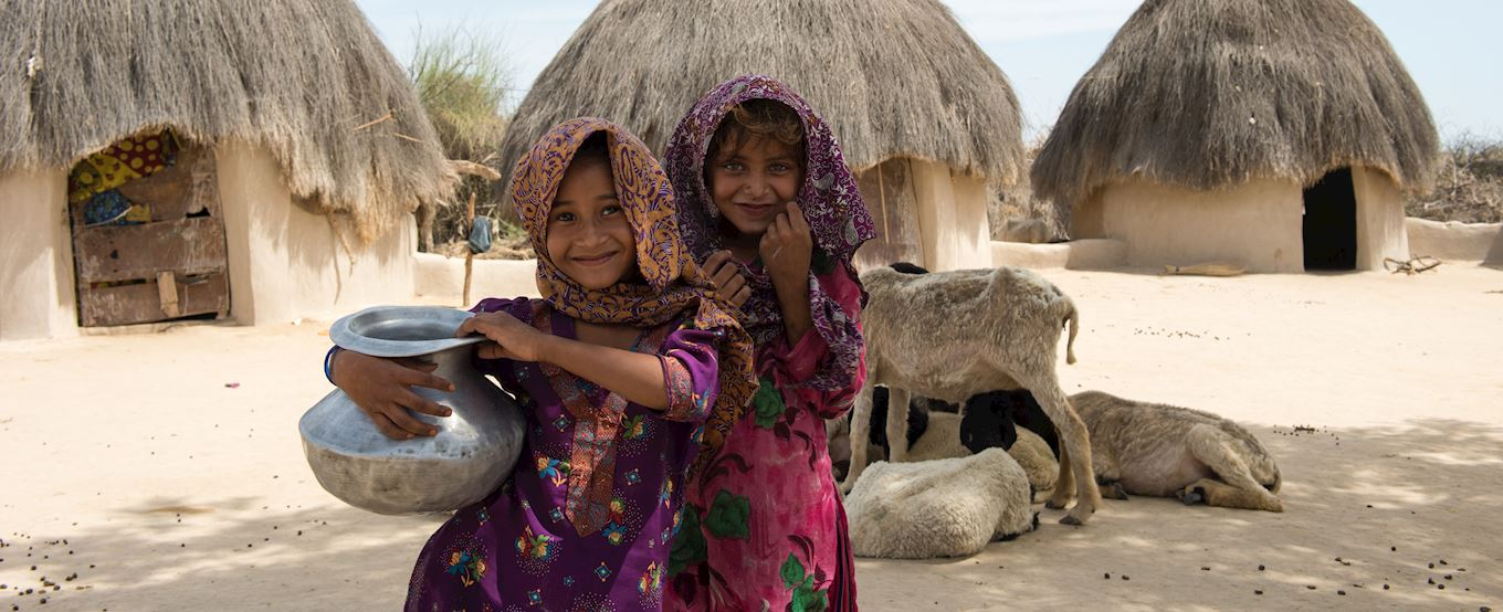 Two young girls holding a water pot