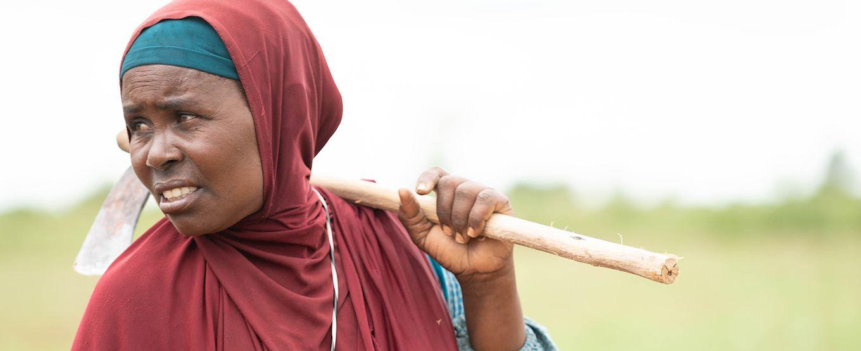 women carrying a hoe in a field